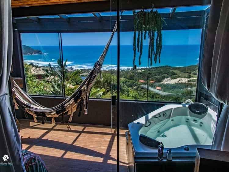 Varanda envidraçada da Cabana Rosa Norte, com banheira de hidromassagem e vista para o mar.